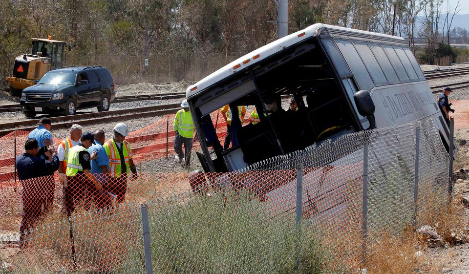 Investigators examine a bus that crashed along the side of Interstate 210 in Irwindale, Calif. on Thursday, Aug 22, 2013. The