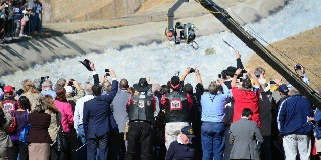 Hats are raised, as are cameras to record a re-enactment of the moment the Los Angeles Aqueduct gates were first opened 100 y