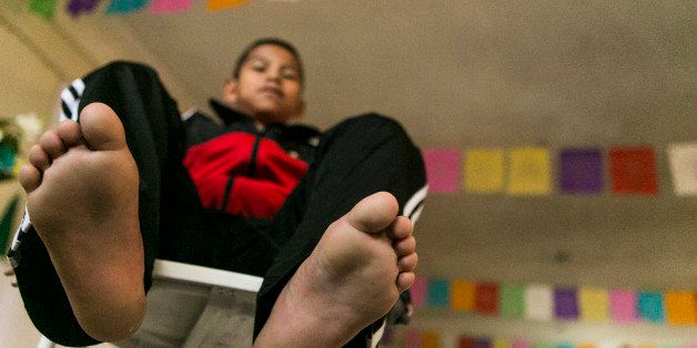 Malquiades Ramirez de Jesus, 10 from El Rastrojo village near San Juan Copala, Oaxaca takes his tennis shoes off, during an a