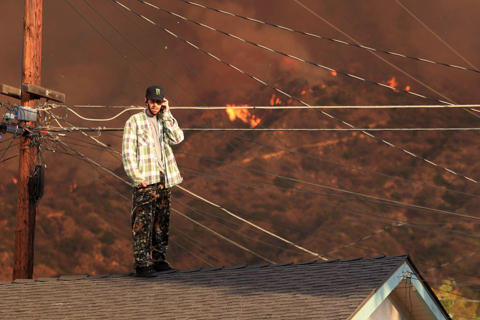 A resident on the roof of a house talks on the phone as a wildfire burns in the hills just north of the San Gabriel Valley co