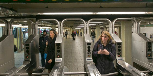 In this Dec. 4, 2013 photo, people move through the turnstiles in the subway in New York's Times Square station. Screeching s