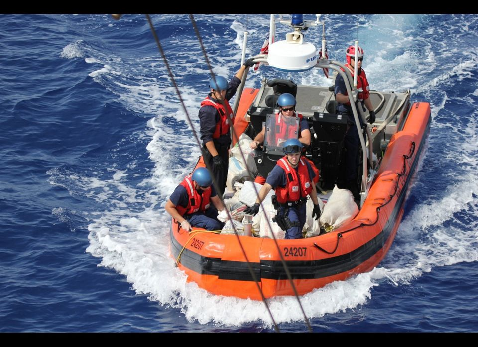 MIAMI -- A Coast Guard Cutter Confidence boatcrew transfers bales of marijuana to the cutter from a 28-foot go-fast vessel in