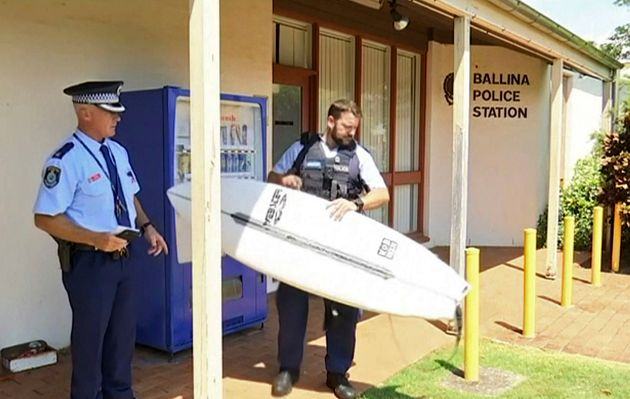 A police officer holds a victim's surfboard at a police station in Ballina,