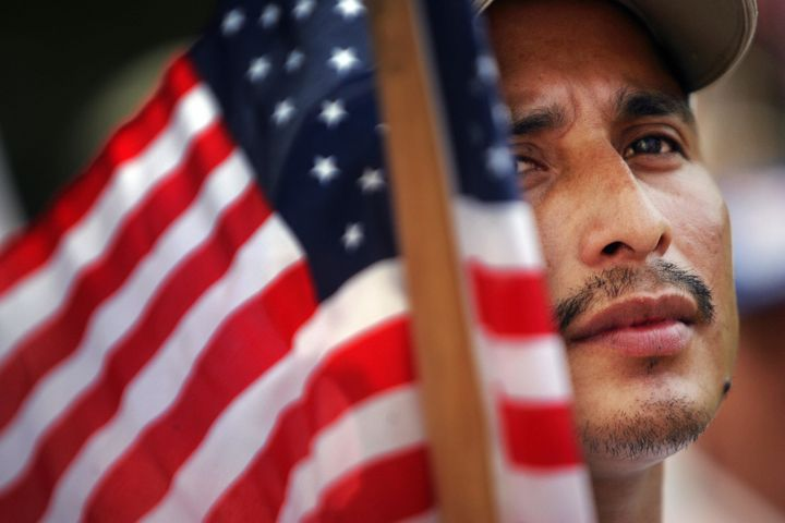 Miami, UNITED STATES: Orlando, an immigrant from Guatemala, holds a US flag as he joined hundreds of other immigrants during