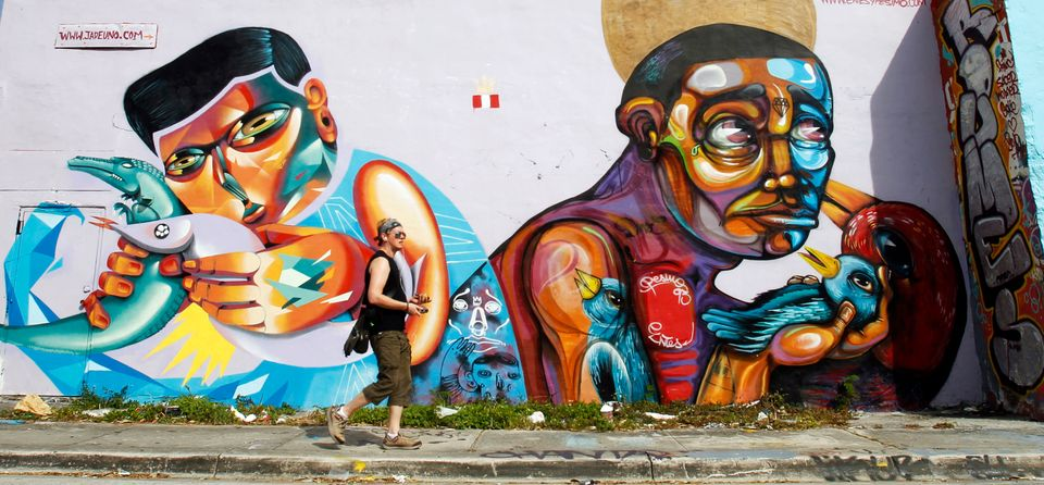 In this Nov. 4, 2012 file photo, an unidentified person walks by a mural in the Wynwood area of Miami. Visiting the Wynwood A