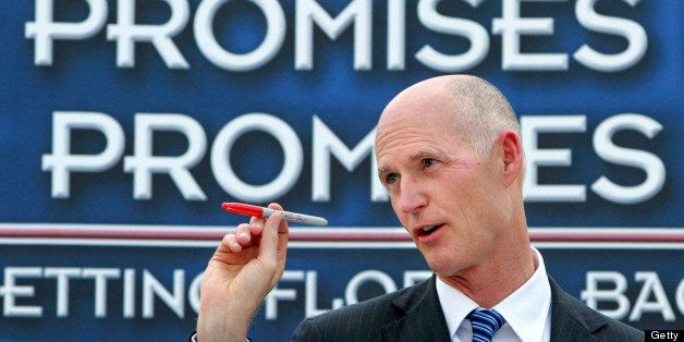 Florida Republican Gov. Rick Scott holds up his red veto pen to make a point during remarks before signing the state budget,
