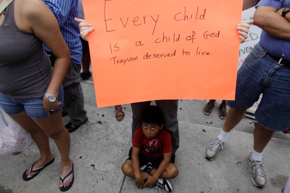 Lucas Boudon sits as his mother Laura Boudon holds up a sign during a vigil for Trayvon Martin at the Torch of Friendship mon