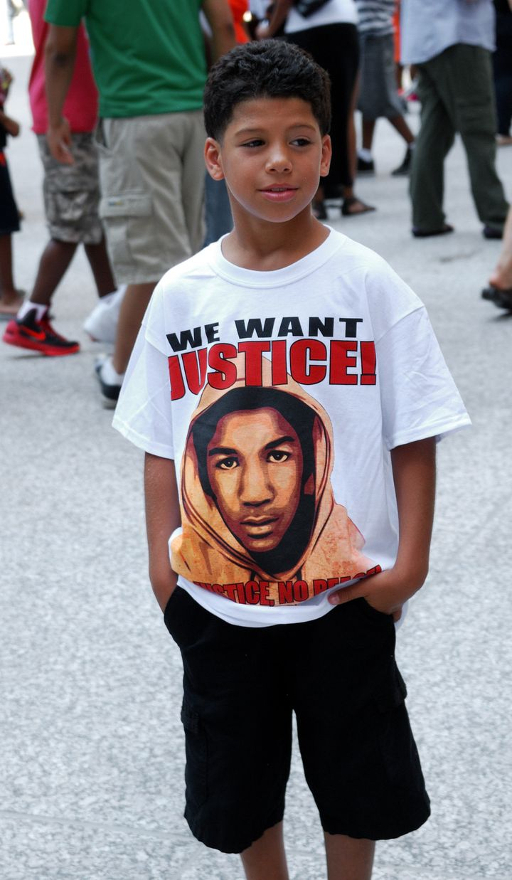 Anthony Simbler, 8, one of dozens of people wearing shirts demanding justice for Trayvon Martin, attends a rally in Chicago o