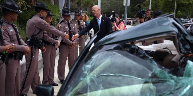 MIAMI, FL - MAY 28:  Florida Governor Rick Scott shakes hands with Florida Highway patrol officers near a wrecked car that is