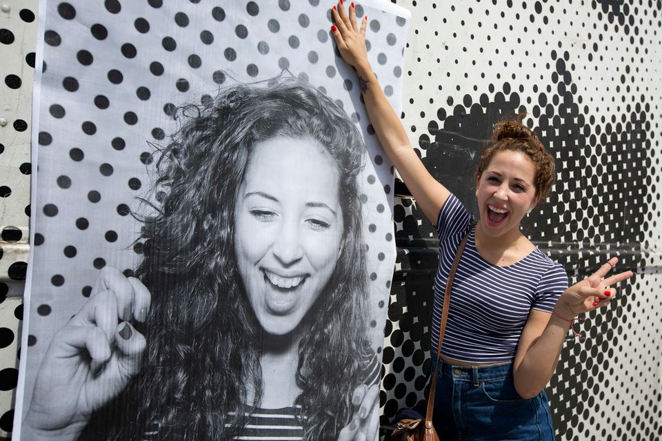 Jessica Rivas poses with her printed photo, Saturday, Aug. 31, 2013 outside the mobile studio, parked in Miami, that is trave