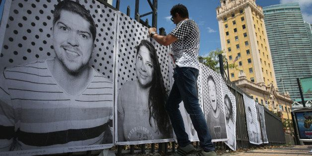MIAMI, FL - AUGUST 31:  Luis Gomez attaches pictures to a fence near the Freedom Tower as he helps hang the 'Inside Out 11M'