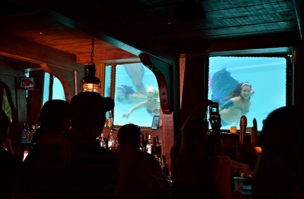 """Every Friday and Saturday at 6:30 p.m., mermaids fill the tank windows at the <a href=""""https://www.facebook.com/WreckBar"""" tar"""