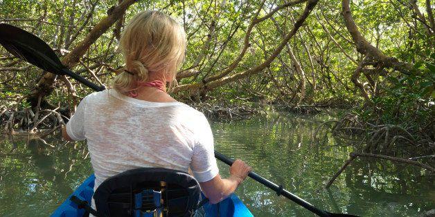 Woman paddles kayak through narrow mangrove canal
