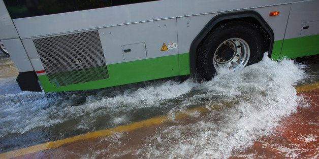 MIAMI BEACH, FL - OCTOBER 18: A public bus stirs up a wake as it drives through a flooded street near where protesters were c