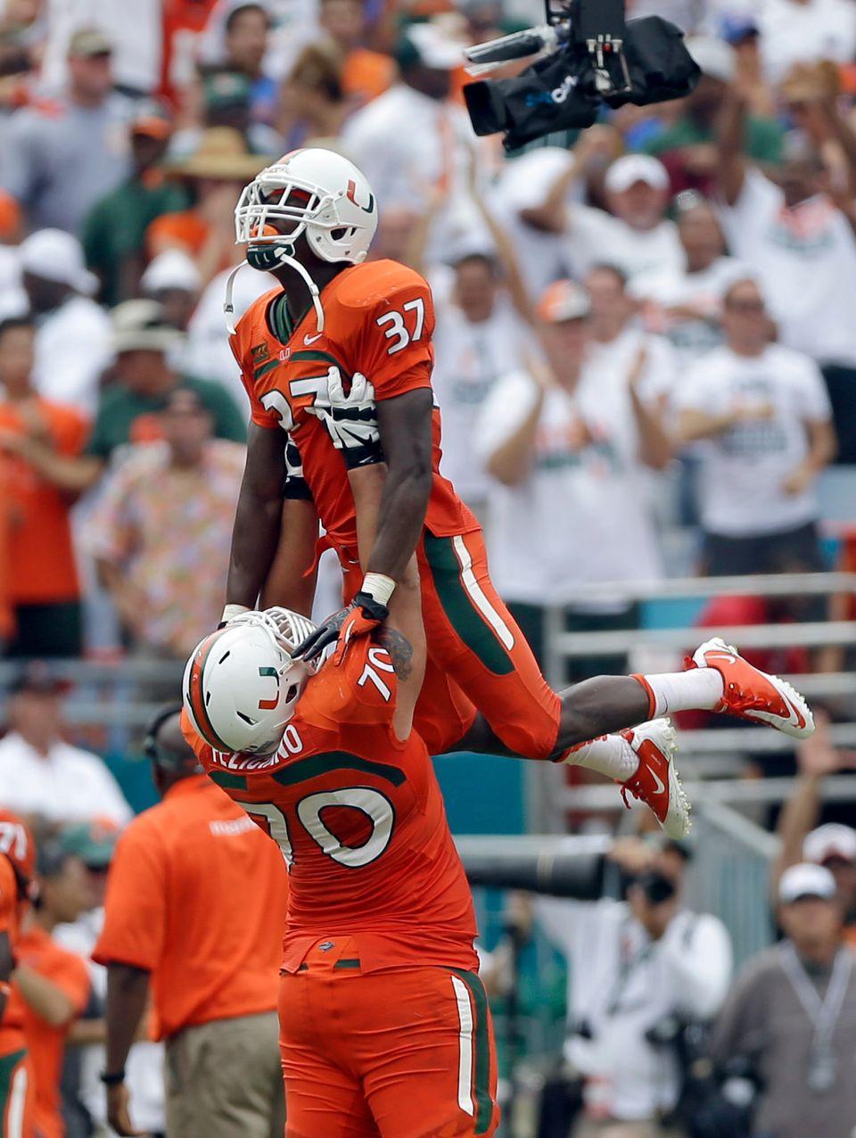 Miami offensive linesman Jon Feliciano (70) and Ladarius Gunter (37) celebrate during the second half of an NCAA football gam