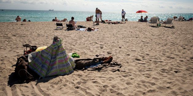 A homeless person lies in the sand in the South Beach neighborhood of Miami Beach, Florida, U.S., on Wednesday, Feb. 20, 2013