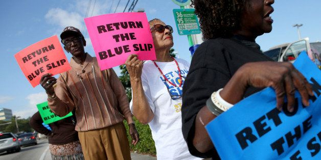 MIAMI, FL - DECEMBER 17:  People gather on the sidewalk in front of the office of Sen. Marco Rubio (R-FL) to ask him to drop