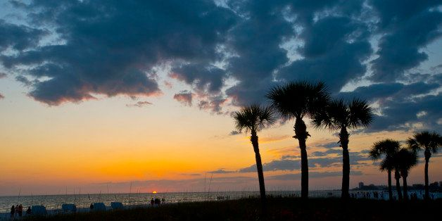 Florida, Siesta Key, Crescent Beach, Palms frame a cloudy dying sunset. (Photo By: Education Images/UIG via Getty Images)