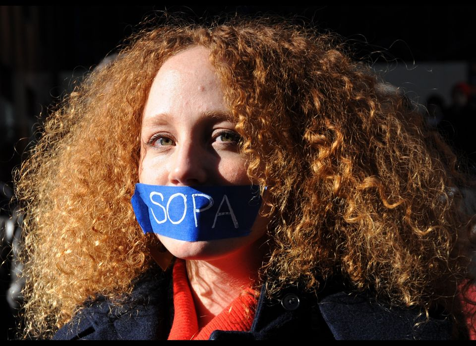 Nadine Wolf wears tape over her mouth as she joins a protest by the technology organization New York Tech Meetup against prop
