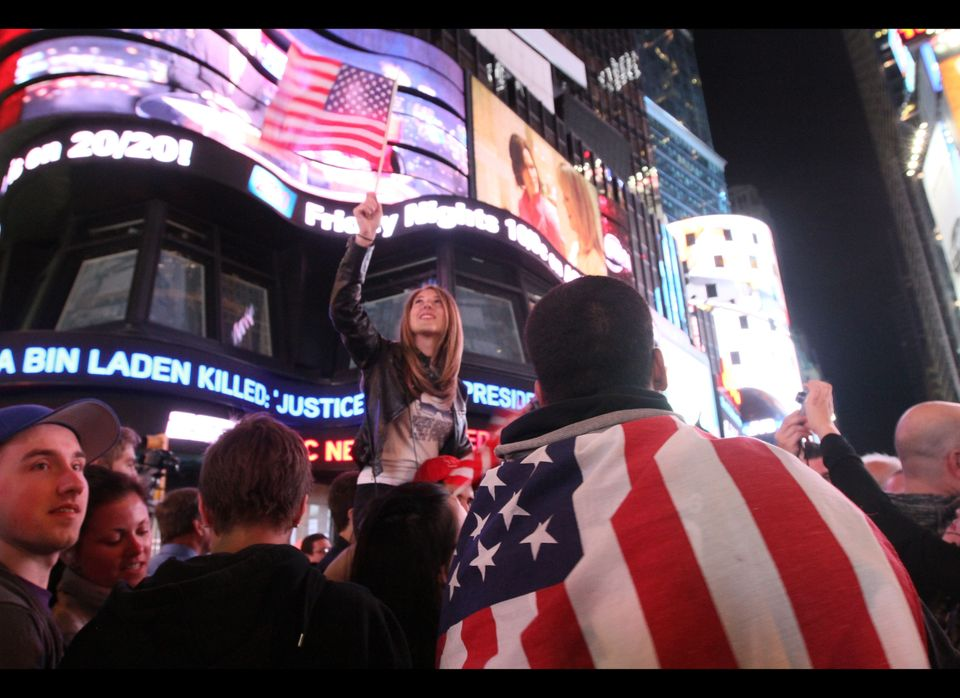 Draped in the American flag, Pedro Valerio, of Elizabeth, N.J., right, and others in New York's Times Square react to the new