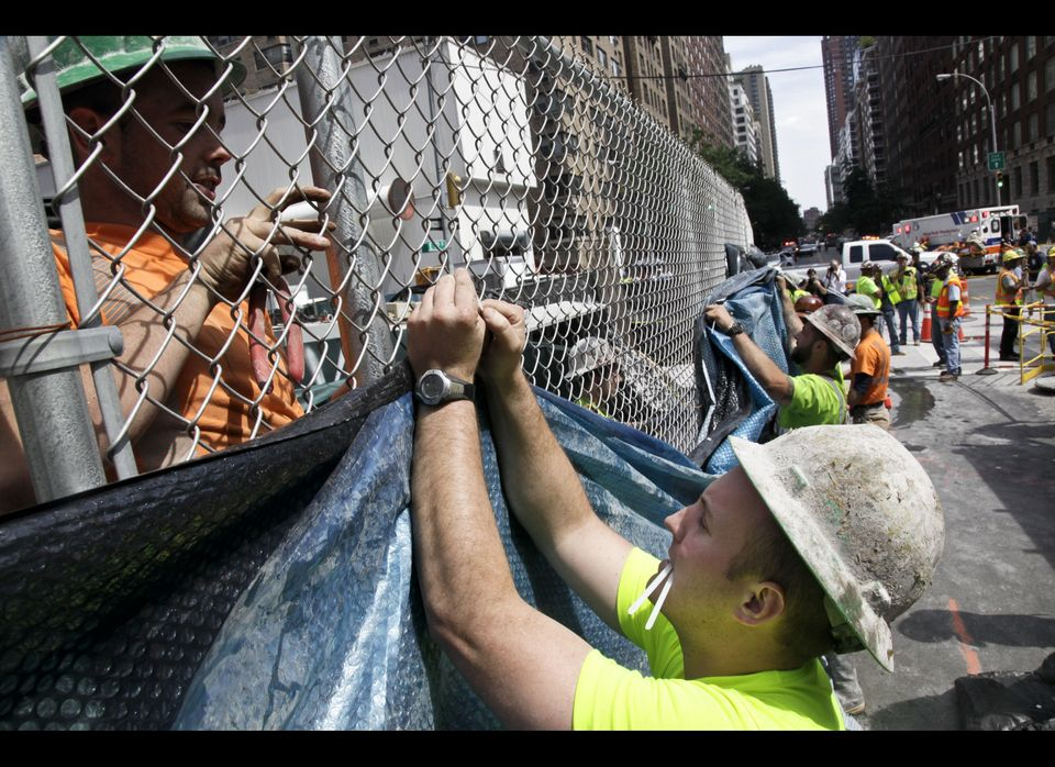 Construction workers hang tarp to block the view of damage following an intentional underground explosion on the Second Avenu