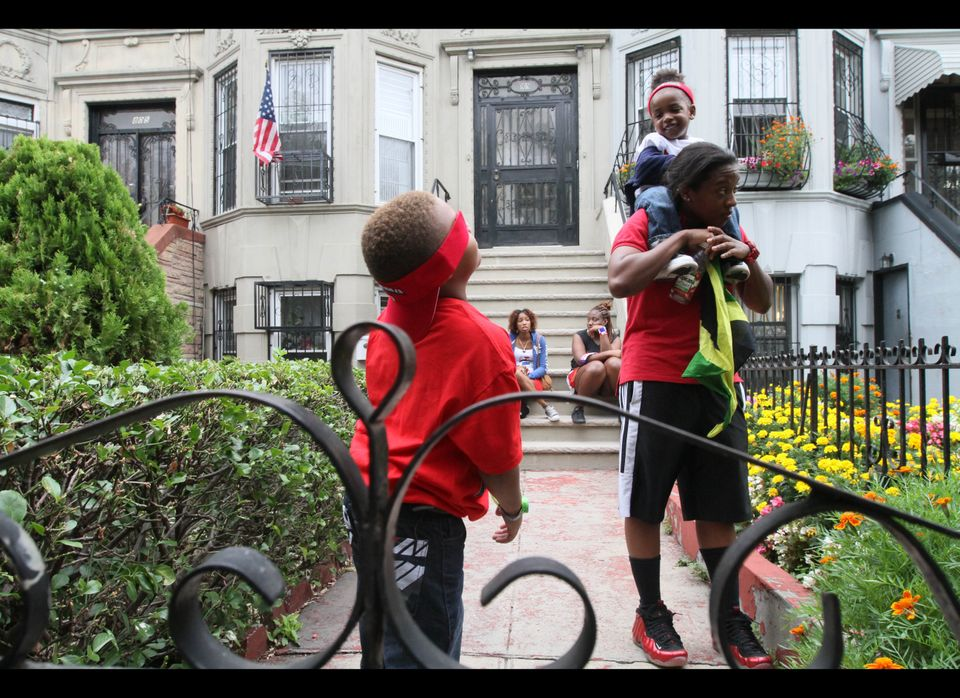 Following the West Indian Day Parade, Melissa Bennett, right, holds her godson Nino G., 2 , on her shoulders as he shares a m