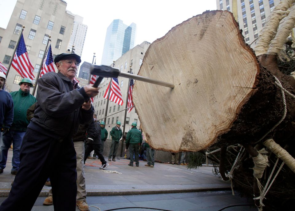 Joseph Balku, of Flanders, NJ, uses a sledge hammer to drive in the spike in the base of the 80th Rockefeller Center Christma