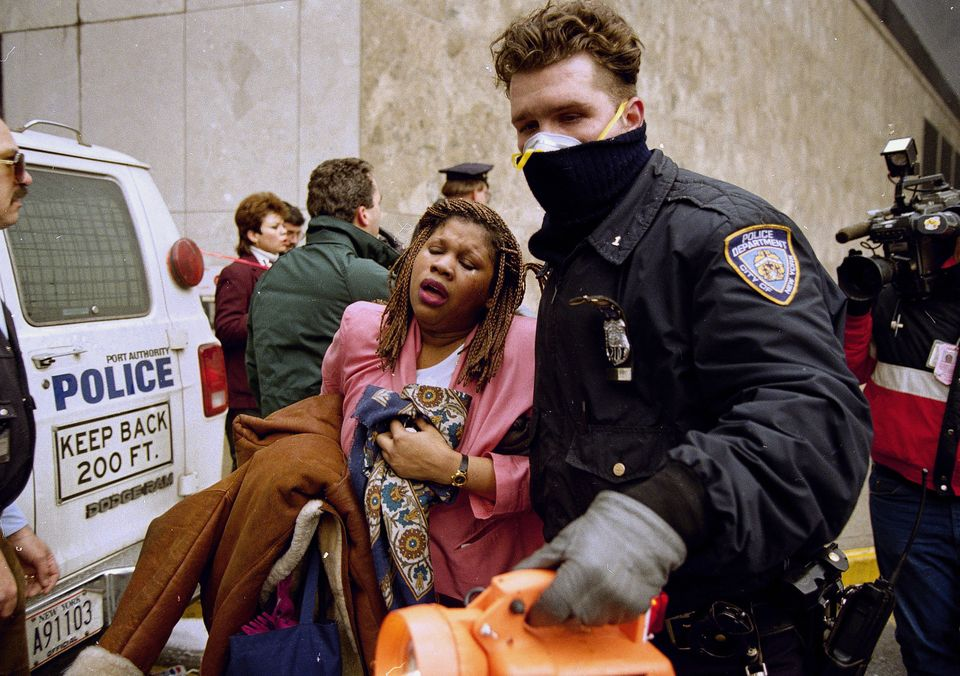 FILE - In this file photo of Feb. 26, 1993, a New York City police officer leads a woman to safety following a bomb blast at