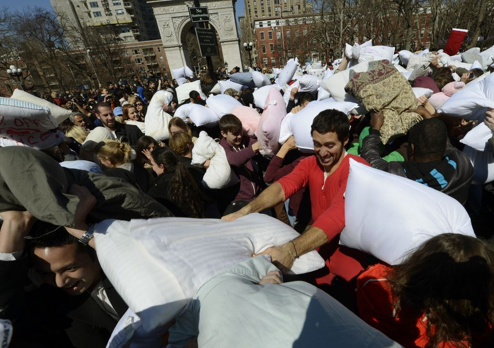 People  hit each other with pillows as they take part in the world's 6th annual Pillow Fight Day  in Washington Square Park i