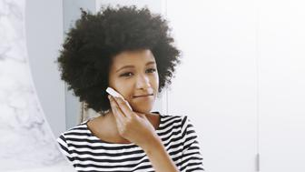 Shot of a confident young woman wiping her face with a cleanser while looking into a mirror in the bathroom at home during the day