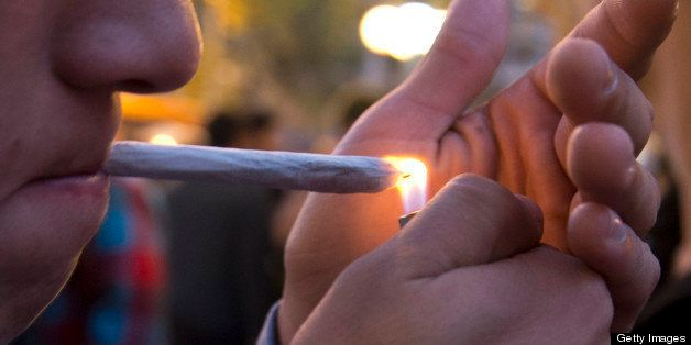 A young man lights a marijuana cigarette during a demonstration demanding a new law on cannabis in Montevideo on May 8, 2013.