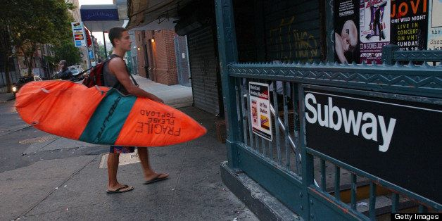 392748 01: Surfer Paul Treacy carries his surfboard to the New York City Subway August 2, 2001 as he starts his hour-long tre
