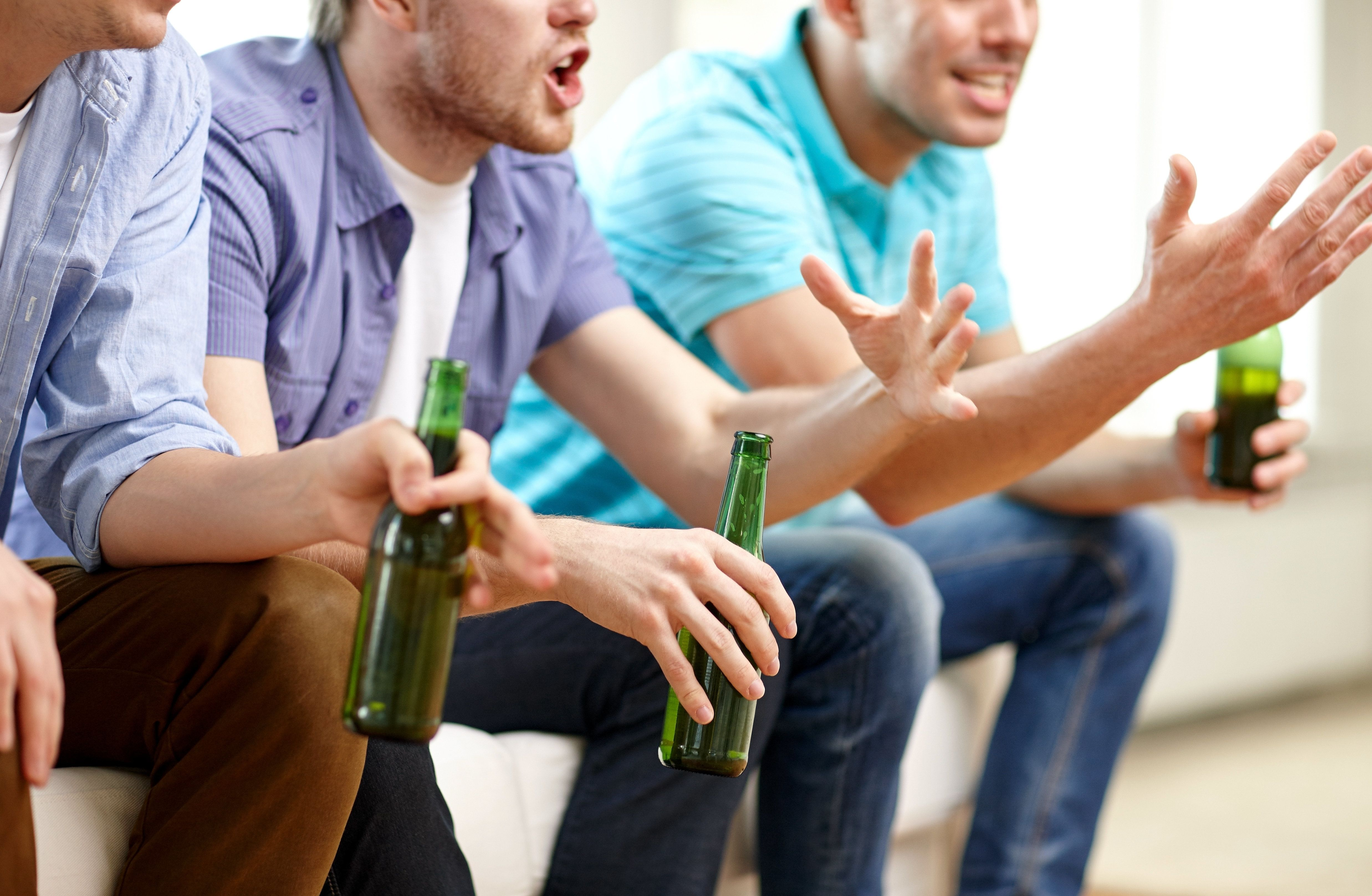 friendship, leisure, people and alcohol concept - close up of happy male friends drinking beer and watching tv at home