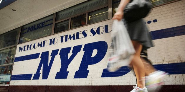 NEW YORK, NY - AUGUST 12: A woman walks by a New York Police Department (NYPD) outpost in Times Square on August 12, 2013 in
