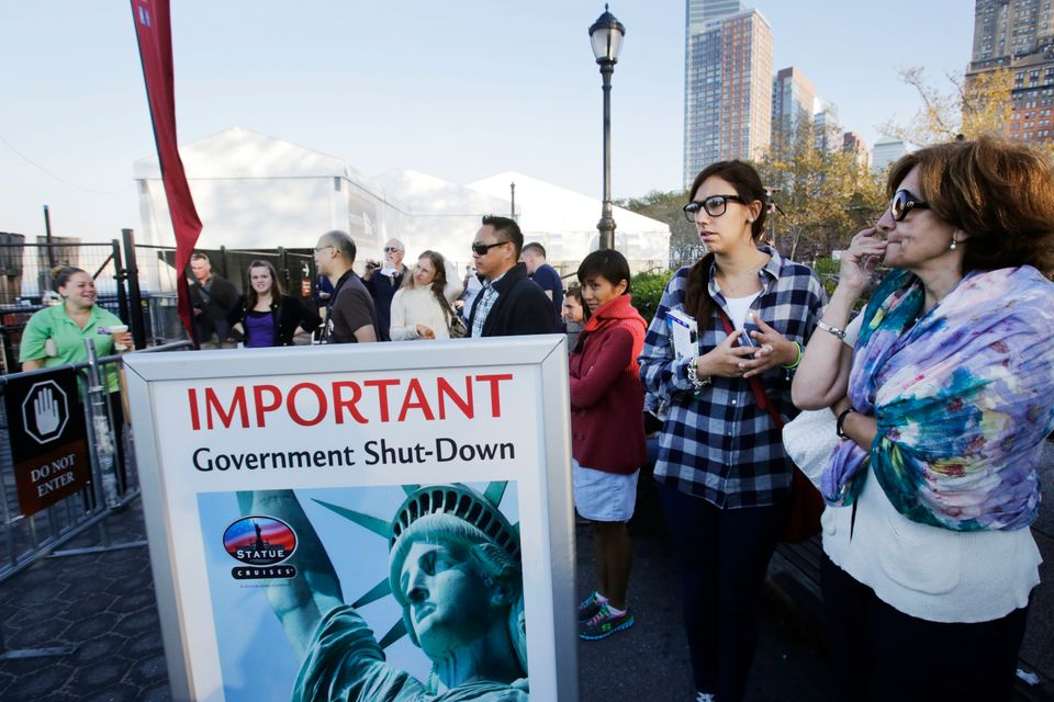 Tourists who had hoped to visit the Statue of Liberty stand near the dock used by Liberty Island ferries, Tuesday, Oct. 1, 20