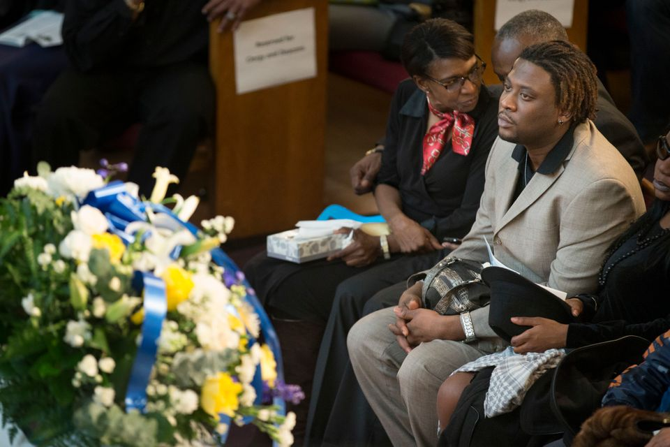 Okee Wade, father of 4-year-old Myls Dobson, sits before his son's casket during a funeral at the First Corinthian Baptist Ch