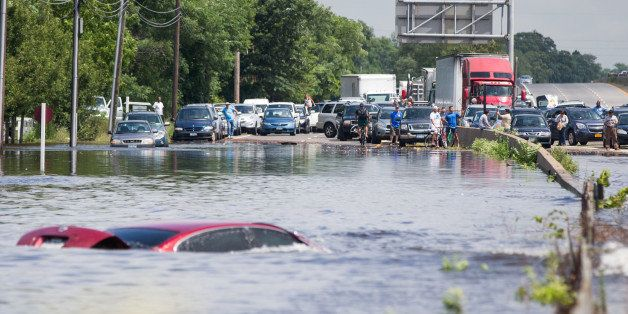 ISLIP, NY - AUGUST 13:   People look on as a car remains flooded on Sunrise Highway at Route 111 following heavy rains and fl