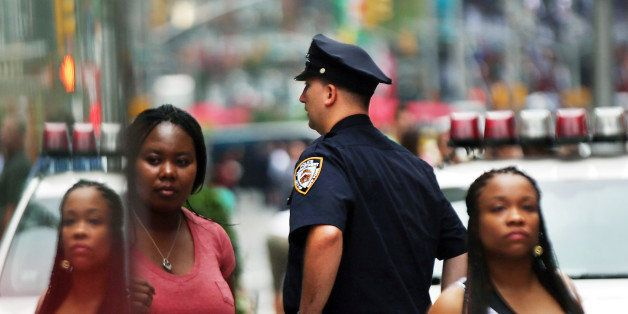 NEW YORK, NY - AUGUST 12: People walk by a New York City police officer in Times Square on August 12, 2013 in New York City.