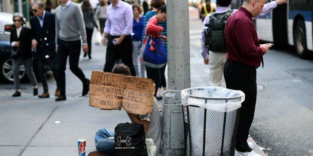 A homeless man with a sign asks for money on a street in New York on October 14, 2014. AFP PHOTO/Jewel Samad        (Photo cr
