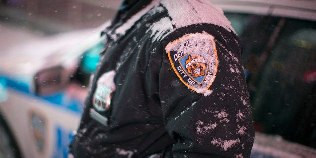 Snow accumulates on an NYPD officer in Times Square, Thursday, Jan. 2, 2014, in New York. The snow storm is expected to bring
