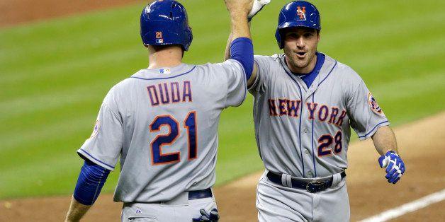 New York Mets' Daniel Murphy (28) is congratulated by teammate Lucas Duda (21), who scored  after Murphy hit a three-run home