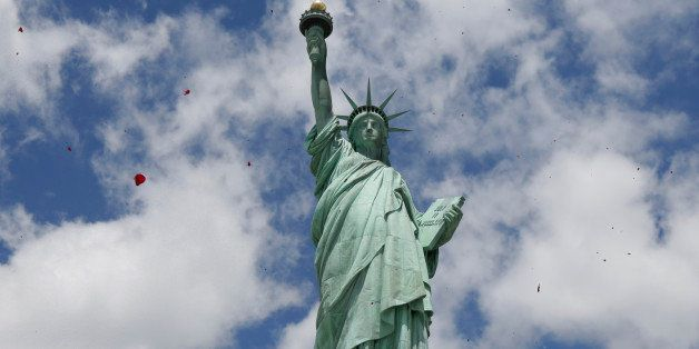 One of three helicopters showeres 1-million rose petals on the Statue of Liberty during a ceremony commemorating the 70th ann