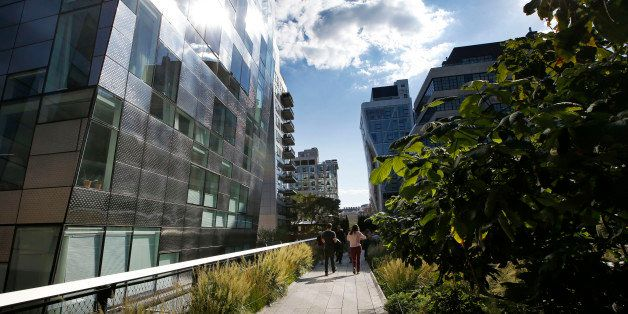 Pedestrians stroll between luxury apartment buildings along the High Line in New York, Wednesday, Sept. 17, 2014. The last st