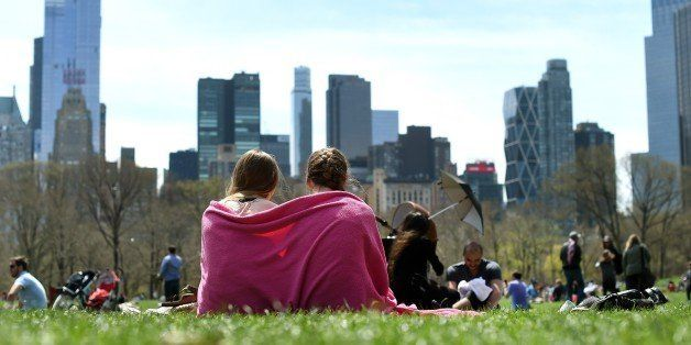 A couple of young girls are wrapped in a blanket on the Sheep Meadow in Central Park  April 19, 2015 as New Yorkers flock out