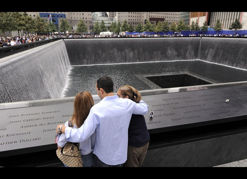 Family members of those who died in the Sept. 11, 2001 World Trade Center attacks, gather at the edge of the north reflecting