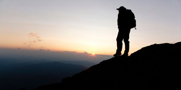 A hiker on the Appalachian Trail at sunset near Mount Clay,  Located in the White Mountains, New Hampshire USA