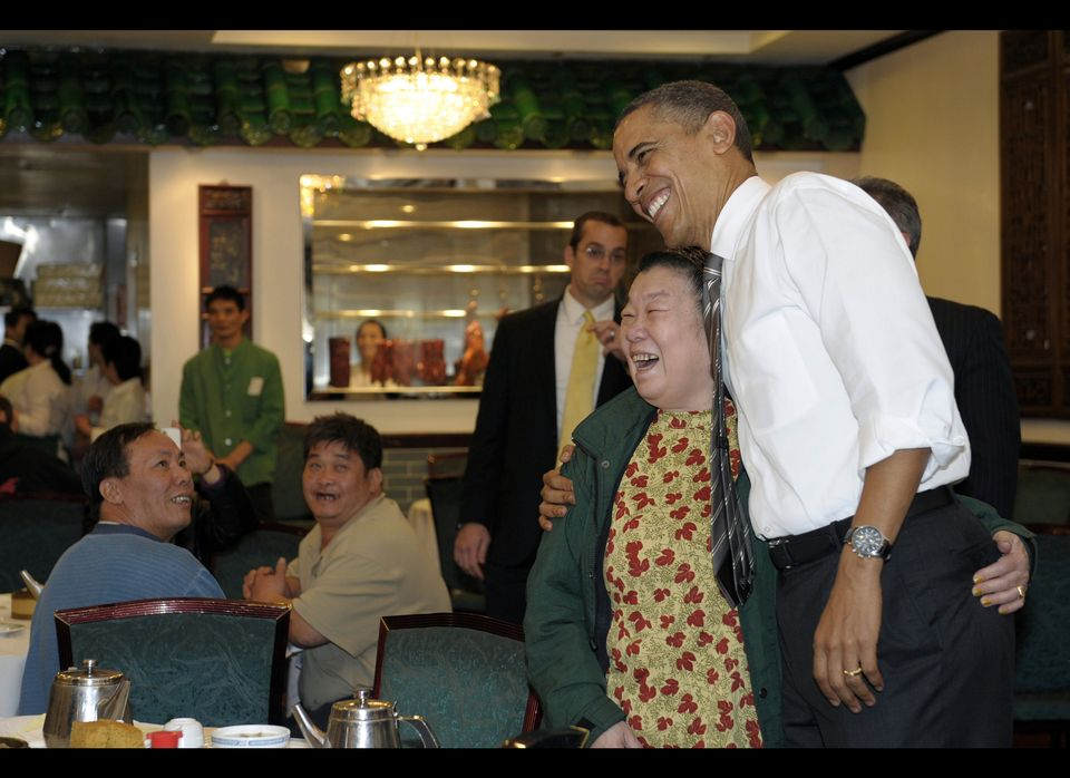 President Barack Obama greets the crowd as he waits for his Chinese food from Great Eastern Restaurant in San Francisco, Thur