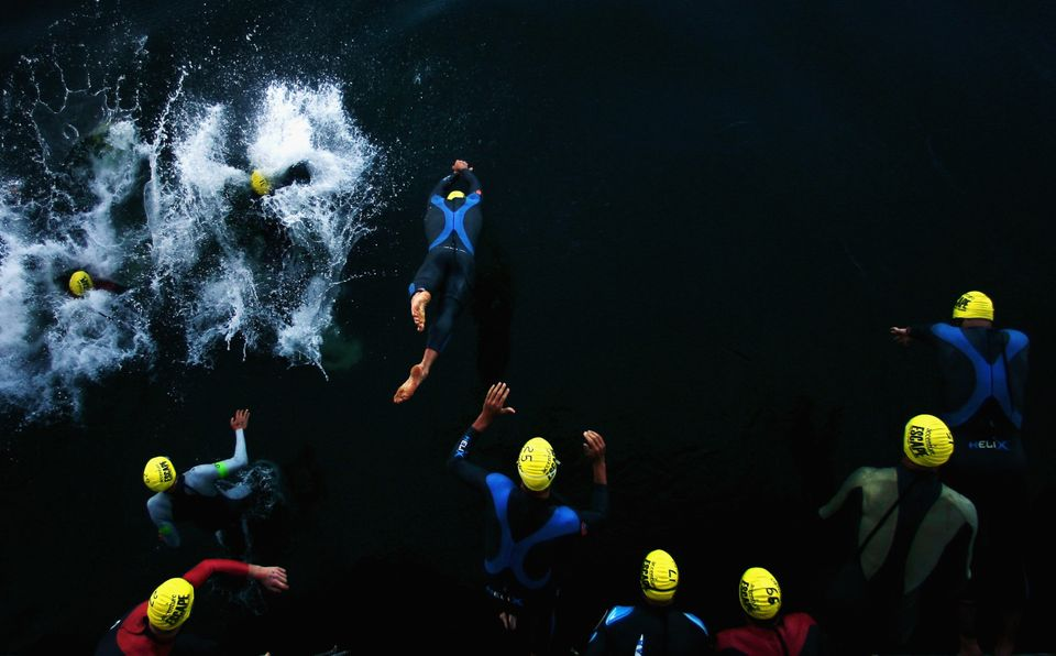 SAN FRANCISCO - JUNE 04:  Competitors enter the water off the start boat at the beginning of the Escape from Alcatraz Triathl