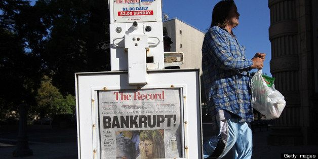 STOCKTON, CA - JUNE 27:  A pedestrian walks by a Stockton Record newspaper rack displaying the headline 'Bankrupt!'  on June