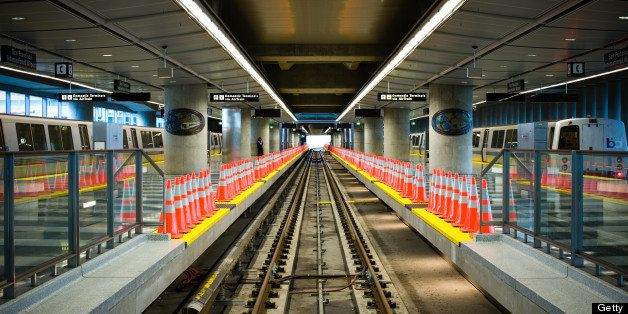 Two Bay Area Rapid Transit (BART) trains flank a closed, empty platform lined with cones while they await passengers at San F